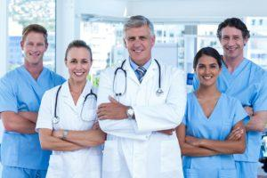 Team of doctors standing arms crossed and smiling at camera in m