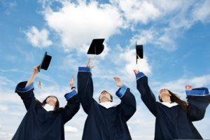 three graduate students tossing up hats over blue sky
